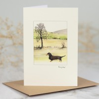 Dog1N - Dachshund by tree and hillslopes Greeting Card